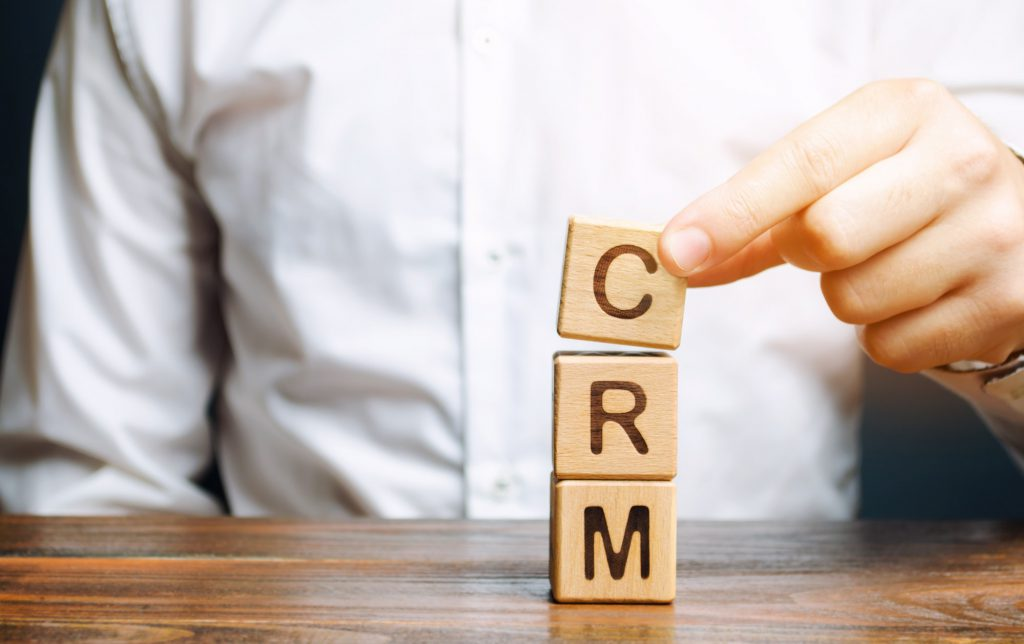 Wooden blocks with the word CRM (Customer Relationship Management) and businessman